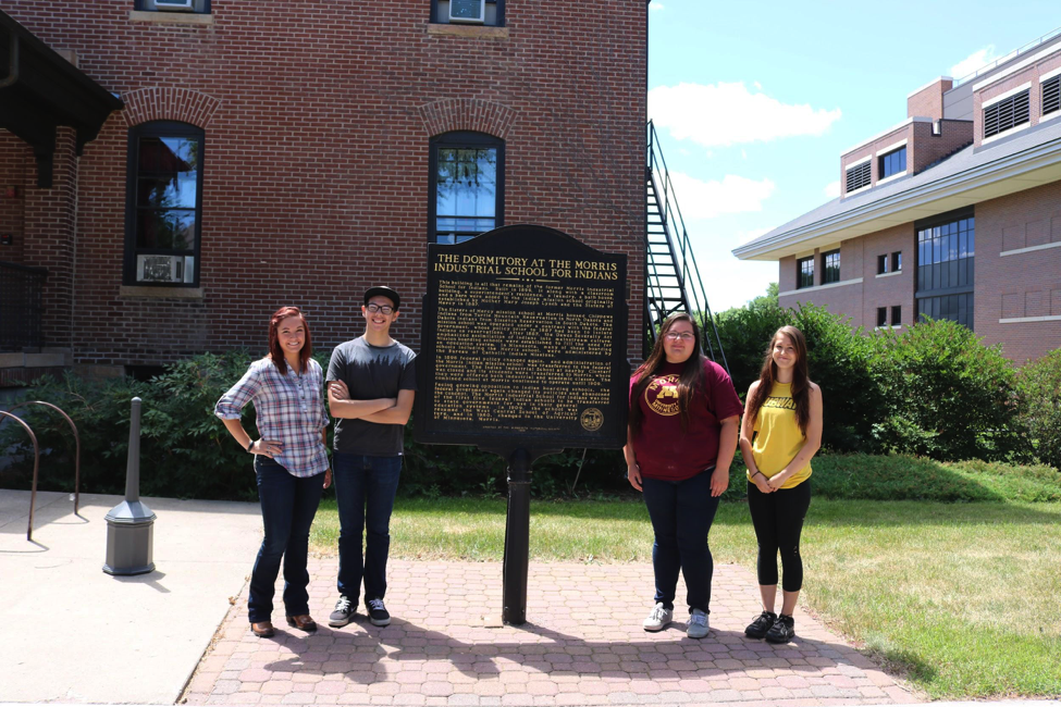 Four students standing outside a historic brick building