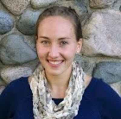 Woman with rock wall as background. Smiling and wearing navy blue shirt with patterned infinity scarf.