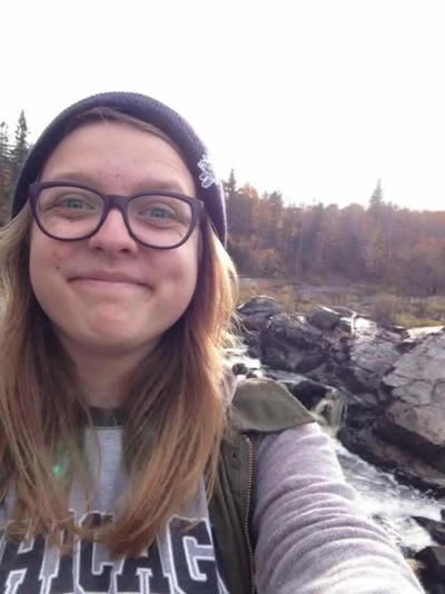 Smiling woman wearing a grey 'Chicago' t-shirt and an army green vest. She has blonde hair and wearing a maroon knitted hat as well as glasses. Her background has tall colorful trees and standing in front of what looks like a river with boulders.