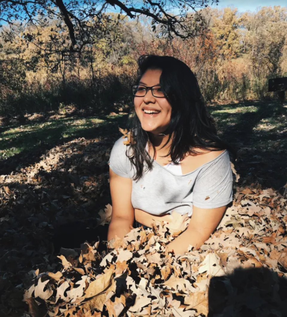 Woman with dark black hair sitting in a pile of dead leaves. She is wearing a grey crop top and black pants, a white bra, and dark black glasses.