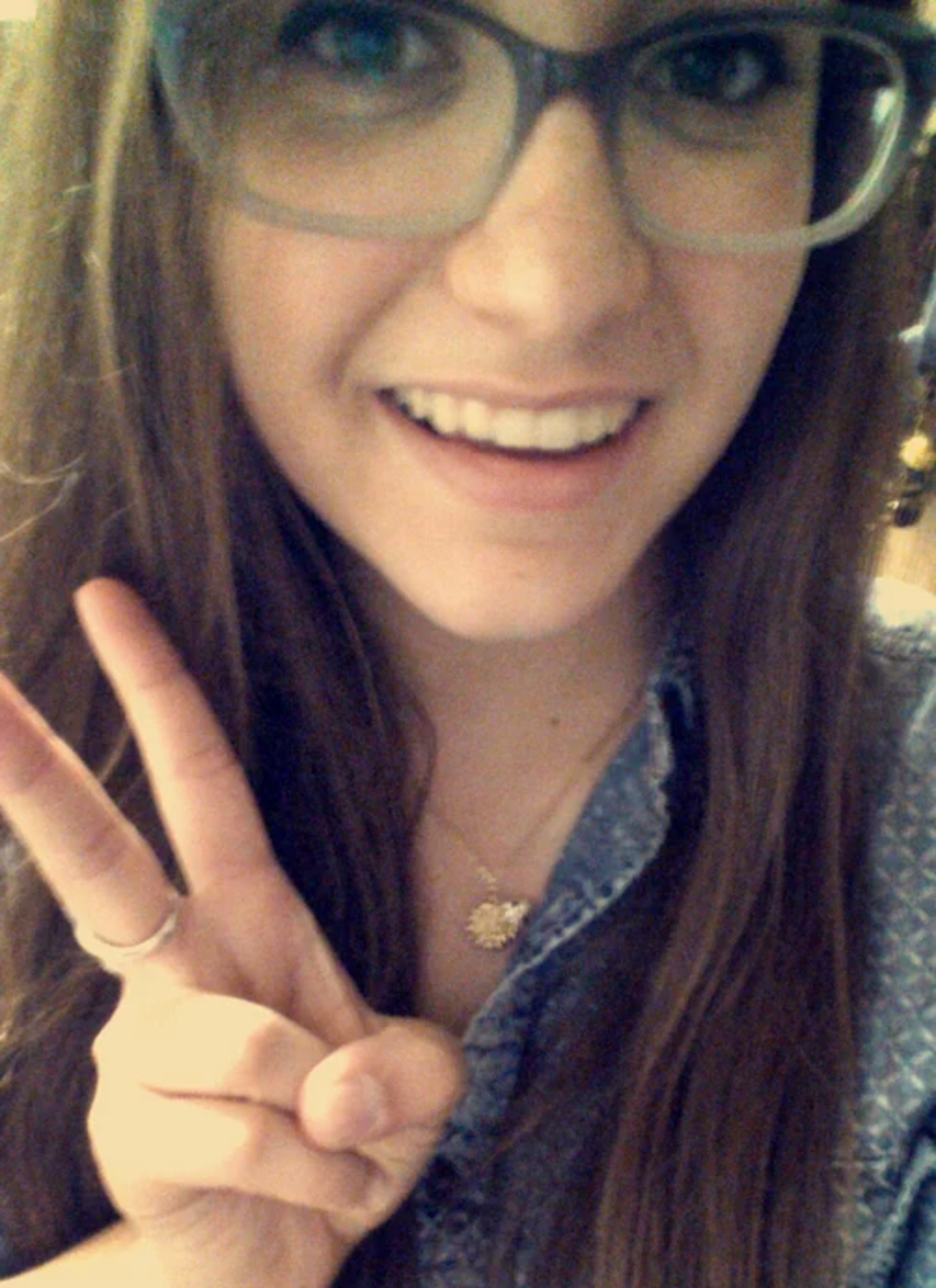 A young brunette woman with peace sign