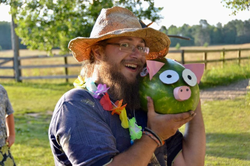 Man wearing a tan cowboy hat, multi-colored lei, and a blue button up shirt with the sleeves rolled up. He is in a grassy area with trees, grassland, and a fence in the background. He is holding up a watermelon with papercutouts pasted to look like a pig