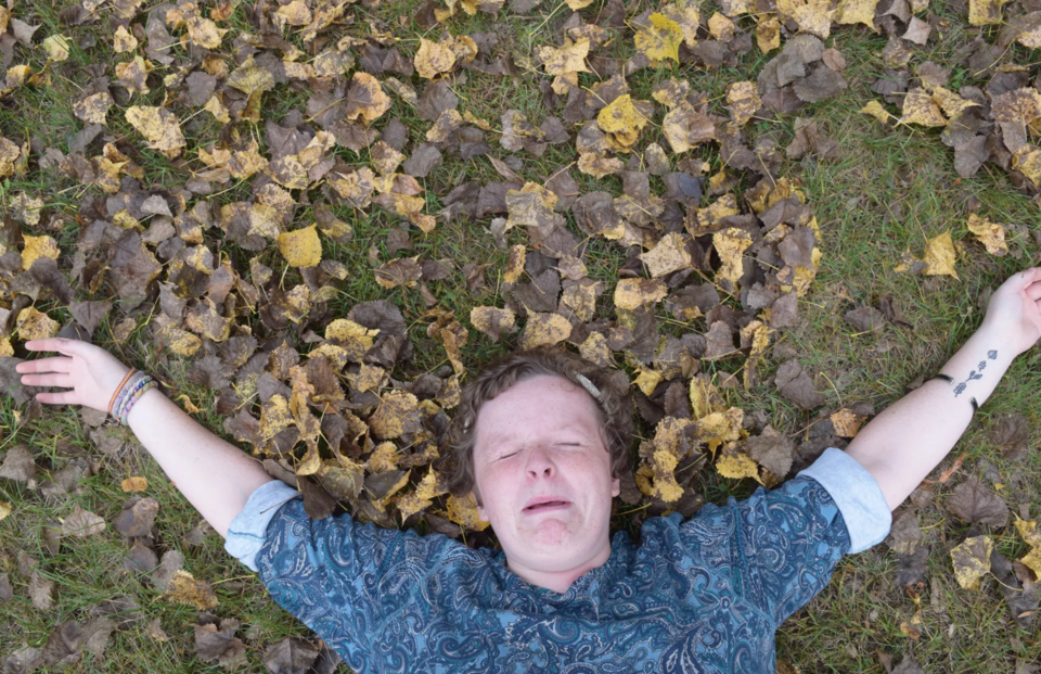Woman making a funny face with her arms spread out and lying on the grass with dead leaves around her. She has short reddish hair and wearing a button up patterned shirt.