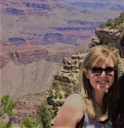 Blonde woman wearing sunglasses and a grey tanktop. She is standing next to someone but they've been cropped out of the photo. Background is plateaus.