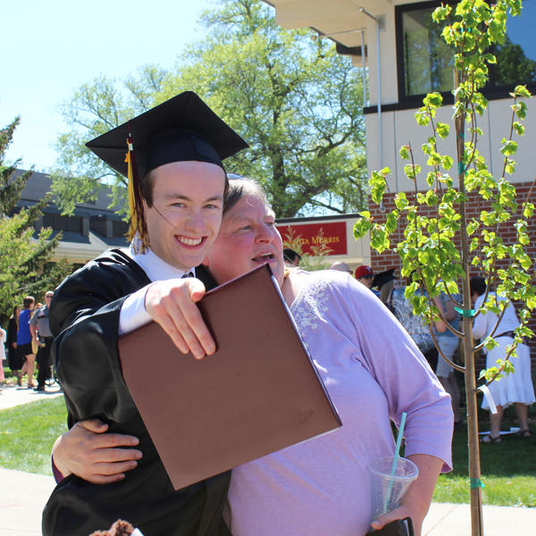 Graduate hugging his mother and looking encouragingly at the camera