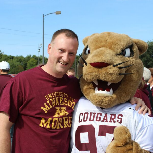 A young alumnus and Pounce the Cougar mascot