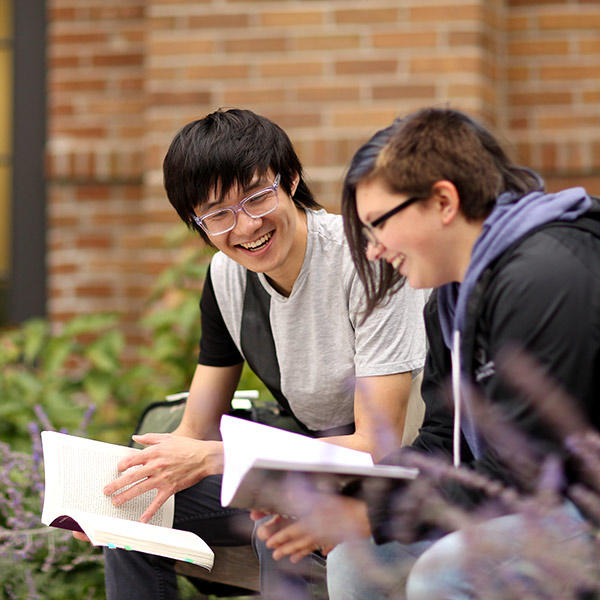 Students reading and laughing on the UMN Morris campus